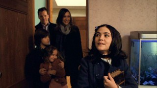 Esther (Isabelle Fuhrman) delights in a look around her new room, while her new family watches on from the doorway.