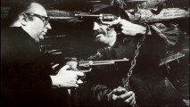 Sergio Leone and Jason Robards draw guns on one another in this Production Gallery photo.