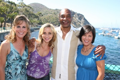 Jodi Benson (voice of Ariel), Tara Strong (voice of Adella, Andrina, and Melody), Samuel E. Wright (voice of Sebastian) and director Peggy Holmes pose for a seaside photo.