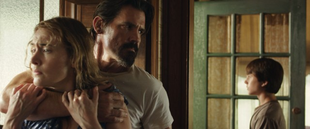 "Escaped convict Frank Chambers (Josh Brolin) grabs hold of Adele Wheeler (Kate Winslet) for appearances while her son Henry (Gattlin Griffith) fends off a neighbor in ""Labor Day."""