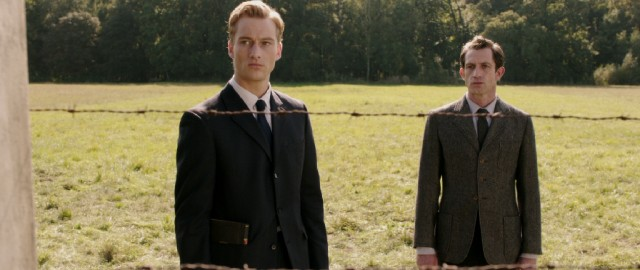 "Johann (Alexander Fehling) and Thomas (André Szymanski) visit Auschwitz to recite the Kaddish for the departed daughters of their friend in ""Labyrinth of Lies."""