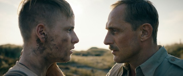 "Sgt. Carl Rasmussen (Roland Møller) shows little mercy publicly for the German boys he oversees at disarming mines in ""Land of Mine."""