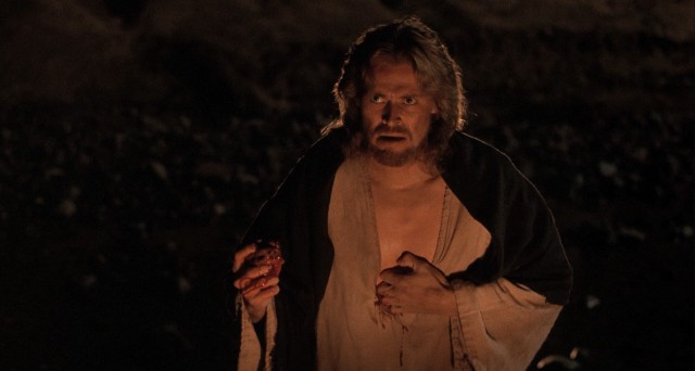Jesus Christ (Willem Dafoe) pulls his bleeding sacred heart from his chest to present it to his followers as a way to convey the importance of love.