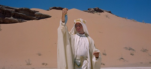 T.E. Lawrence (Peter O'Toole), a.k.a. El Aurens, admires his new white clothes in the reflection of his dagger.