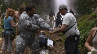 "A man in a padded gray suit playing an ape gets a costume adjustment in the ""Tarzan vs. Akut"" behind-the-scenes short."