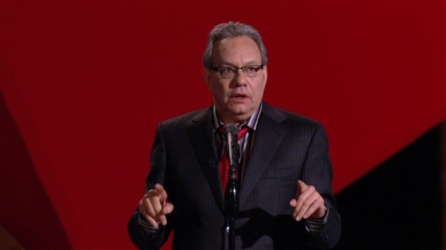 "Lewis Black performs in front of a giant suspended red cube in his stand-up comedy special ""In God We Rust."""