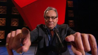 "With fingers extended toward the camera, Lewis Black advertises ""In God We Rust"" as a 3D presentation, which it is not."