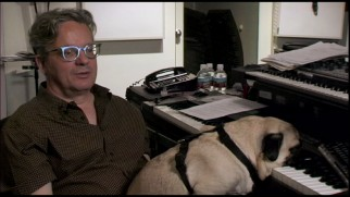 While Mark Mothersbaugh discusses his Wes Anderson scores, Mothersbaugh's dog rests his head on a keyboard.