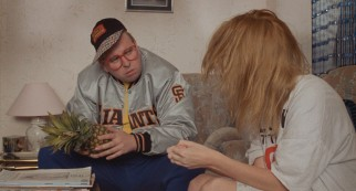 Nicola watches as boldly-fashioned family friend Aubrey (Timothy Spall) fidgets with a pineapple.
