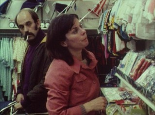 "A couple (Richard Ireson and Celia Quicke) shops for baby clothes in Mike Leigh's 1975 short ""The Birth of the Goalie of the 2001 F.A. Cup Final."""