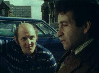 "A man (Robert Putt) delays his cinema-bound neighbor (Tim Stern) with small talk in the Mike Leigh Five-Minute Film ""Old Chums."""