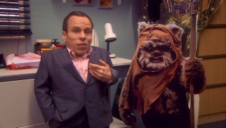 Warwick Davis proudly stands next to cardboard standee of his Return of the Jedi Ewok, Wicket, while pointing out George Lucas was wrong to hide his face in the role.