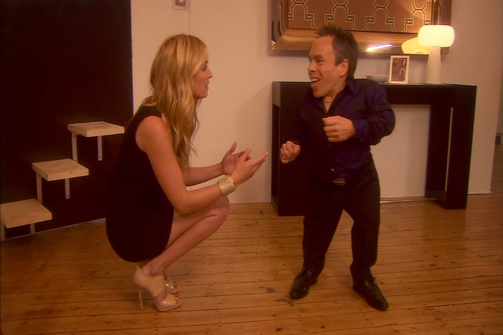 Cat Deeley, paid to be the only real celebrity guest at Warwick Davis' housewarming party, crouches down to get her story straight.