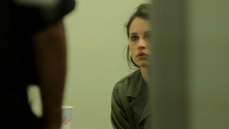Anna's (Felicity Jones) airport detainment by immigration officers is artistically shot from a distance from a partially obscured angle.