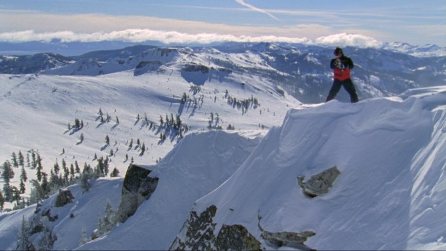 "A skier checks out the view from a steep, perilous mountain in ""Warren Miller's ...Like There's No Tomorrow."""