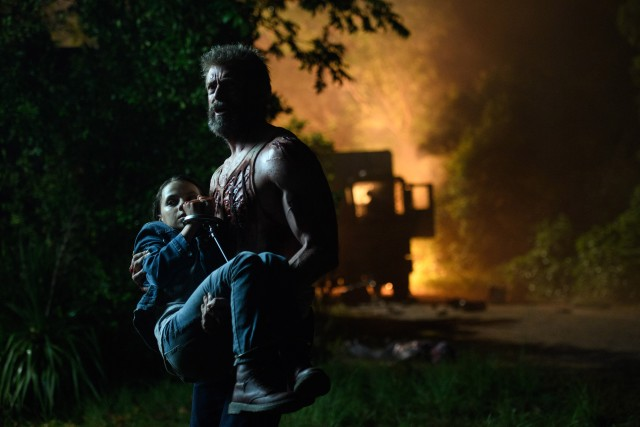 "A bloodied Wolverine (Hugh Jackman) clutches to his fierce daughter Laura (Dafne Keen) in ""Logan."""