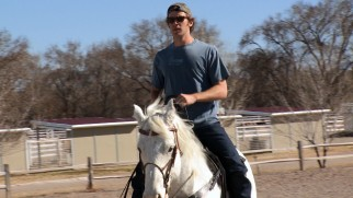 At Cowboy Boot Camp, Armie Hammer learns to ride a horse like a real cowboy with sunglasses and a backwards baseball cap.