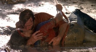 J.J. McQuade (Chuck Norris) gets down, dirty, wet, and wild with his widowed love interest (Barbara Carrera).