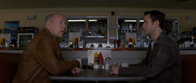 "An older (Bruce Willis) and younger (Joseph Gordon-Levitt) version of the same character share a meal and chat at a diner in ""Looper."""