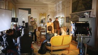 "Whit Stillman prepares the actors for a shot in ""Behind the Scenes: Love & Friendship."""
