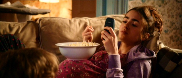 "Rosie (Lily Collins) uses her pregnancy bump to balance a bowl of popcorn in ""Love, Rosie."""