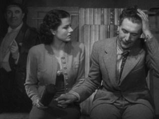 Iris (Margaret Lockwood) and Gilbert (Michael Redgrave) catch their breath after a row with Italian magician Signor Doppo (Philip Leaver in cardboard standee form).