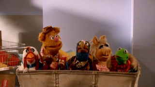 "Shenanigans leave Camilla, Rizzo, Fozzie, Pepe, Gonzo, Miss Piggy, and Kermit in a mail cart in ""A Muppets Christmas: Letters to Santa."""