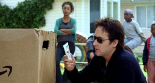 If John Cusack seems overly communicative towards this large Amazon.com box, it's because there's a potential son inside.