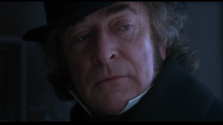 After a song establishes his not-so-great reputation, Michael Caine makes his first clear appearance as miserly protagonist Ebenezer Scrooge.
