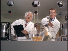 At his workplace, Albert (Dean Jones, right) tries to encourage a dim-witted duck to pass one of Dr. Gottlieb's tests.