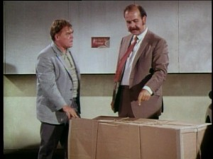 Foley (Mickey Shaugnessy) and McClure (Roger C. Carmel) think the dog has their necklace and is in the cardboard box.