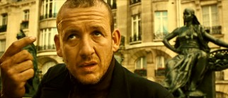 Gunshot-wounded Bazil (Dany Boon) explains his condition to spared ex-con Slammer, who refers him to a potential adoptive family.