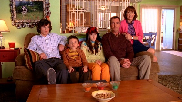 The Hecks -- Axl (Charlie McDermott), Brick (Atticus Shaffer), Sue (Eden Sher), Mike (Neil Flynn), and Frankie (Patricia Heaton) -- try to look like the perfect family for a social worker visit.