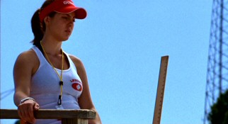 Grace Berry (Eva Amurri) carries a yardstick at her summer job as a water park lifeguard with which to ensure kids meet the water slide's minimum height requirement.
