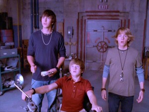 In Room 77, the bomb shelter they have all to themselves, Zeke (Nicholas Braun), Charlie, and Virgil have their faces lit with the cool colors of time travel.
