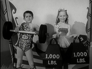Cubby seems to be struggling with this dumbbell, but Karen has no problem holding a ton of bags. Why, it must be Circus Day!