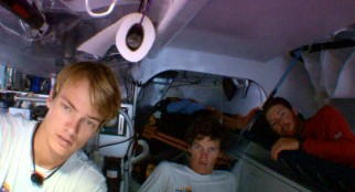 Inside the ship's hull, three leading crew members observe and discuss the Morning Light's navigational path.