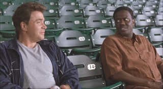 Stan and his best friend Boca (Michael Rispoli) sit in emptied bleachers.
