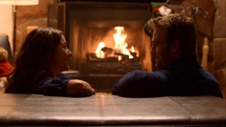 Reba (Erin Karpluk) and Seth (James Van Der Beek) get cozy in front of the fireplace, as lovers are known to do at Christmastime.