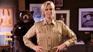 In front of a stuffed bear and transgendered Photoshop jobs, Miss Hulka (Jane Lynch) of Hulka's Rock stands proudly.