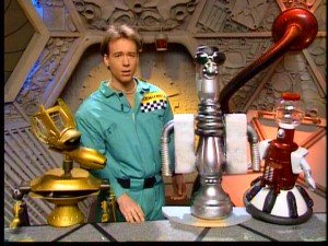 At the prompting of his robot buddies, series creator and original host Joel Hodgson tries asking a question of a state-of-the-art new bot.