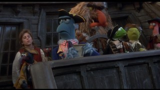 Jim Hawkins (Kevin Bishop) and assorted Muppets stand on the Hispaniola for roll call with Mr. Arrow (Sam the Eagle).