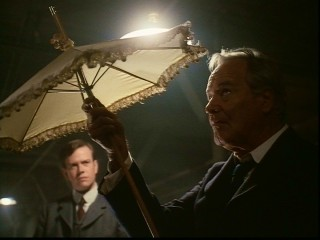 Though it doesn't look like rain, Governor Slaton (Jack Lemmon) checks out Mary Phagan's umbrella, while his speechwriter/assistant (Dylan Baker) looks on.