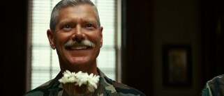 "Fresh flowers bring a big smile to the face of Brigadier General Dean Hopgood (Stephen Lang of ""Avatar"" fame)."