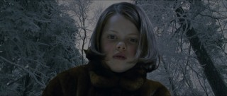 Lucy (Georgie Henley) looks at a frozen fish in this not-quite-finished looking addition.