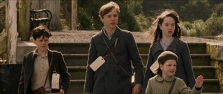 The four Pevensie children -- Edmund (Skandar Keynes), Peter (William Moseley), Susan (Anna Popplewell), and Lucy (Georgie Hensley) -- wait for their ride at the train depot.