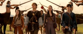 The Pevensie children (Georgie Henley as Lucy, William Moseley as Peter, Anna Popplewell as Susan, and Skandar Keynes as Edmund) are proud to get a royal welcome in Narnia, where they're recognized as kings and queens.