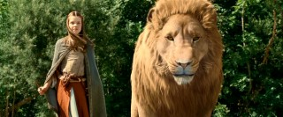 Lucy (Georgie Henley) and Aslan the Lion stand together at one end of a bridge.
