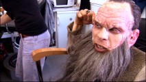 Having completed another day of work, Warwick Davis eagerly peels off his latex face mask.