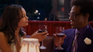 A glass of wine between two friends is ruined by a gaudy purple suit. Oh well, if it spills, it'll blend!